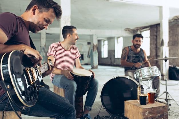 Powtórka zespołu muzyki rockowej. gitarzysta basowy, gitarzysta elektryczny i perkusista na poddaszu. koncepcja muzyki rockowej i jam session. pasja do muzyki i koncepcji kultury młodzieżowej