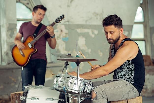 Powtórzenie zespołu muzyki rockowej. gitara elektryczna i perkusista za zestawem perkusyjnym.