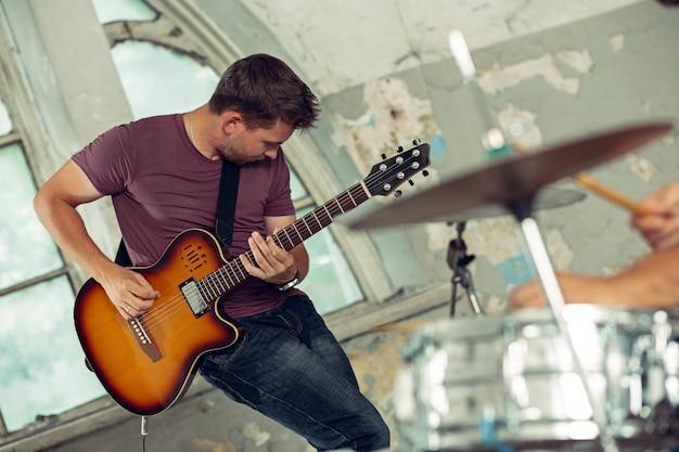 Powtórzenie zespołu muzyki rockowej. gitarzysta elektryczny i perkusista za zestawem perkusyjnym.