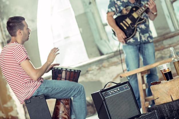 Powtórzenie zespołu rockowego. gitarzysta elektryczny i perkusista za zestawem perkusyjnym.