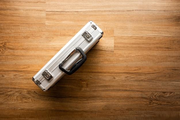 Powyżej metalowej teczki (pudełko) na tle drewnianej podłogi. pomysły na narzędzia i koncepcje bezpieczeństwa