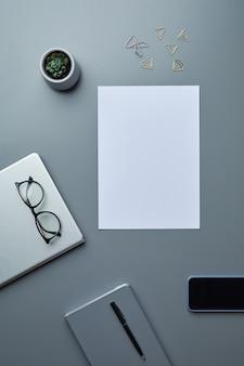 Powyżej płaski układ pustego białego papieru na szarym tle miejsca pracy ze smartfonem i akcesoriami biznesowymi,