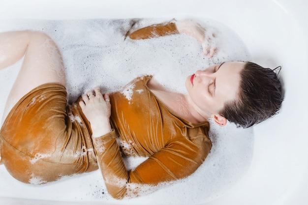 Powyżej portret młodej kobiety dorosłej leżącej w wannie wypełnionej węglową bombą do kąpieli