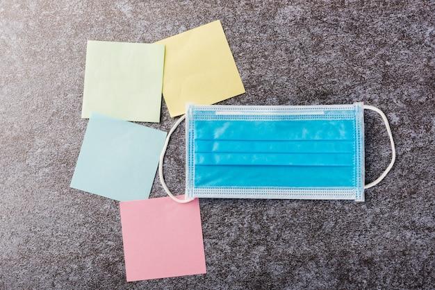 Powyżej pusta lista karteczek w kolorze żółtym, zielonym i niebieskim z ochronną maską na twarz