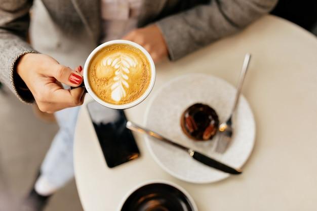 Powyżej ramki młoda kobieta trzyma filiżankę kawy na zewnątrz kawiarni z deserem