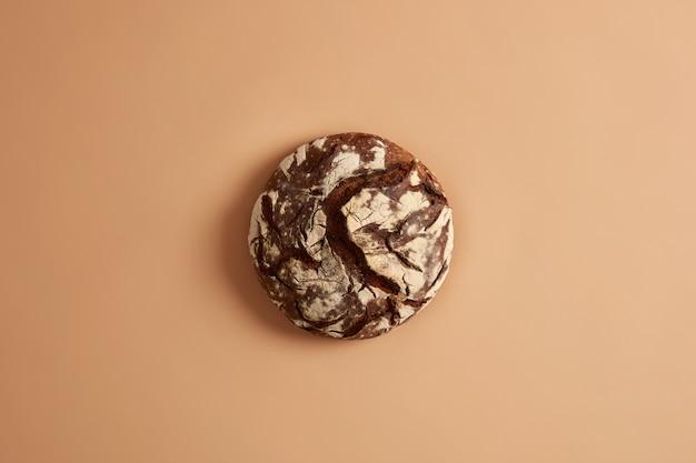Powyżej ujęcie okrągłego wypiekanego pysznego chleba na zakwasie, bezglutenowe, beżowe tło studio. koncepcja zdrowej żywności, diety i odżywiania. gotowanie zbilansowanej żywności. całe ziarna, rolnictwo.