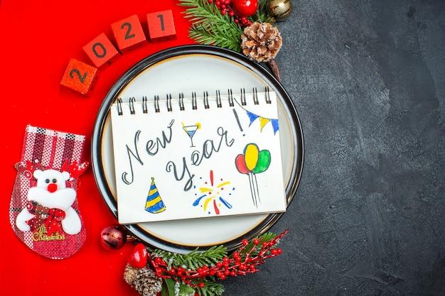 Powyżej widok akcesoriów do dekoracji talerza obiadowego gałęzie jodły i numery świąteczne skarpety na czerwonej serwetce na czarnym tle