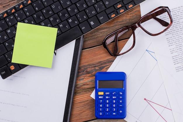 Powyżej widok biurowego miejsca pracy w okularach dokumenty klawiatura niebieski kalkulator