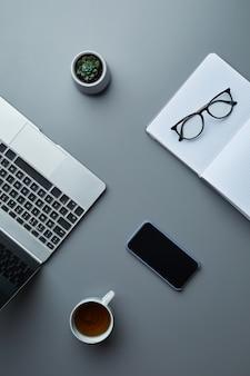 Powyżej widok biznesowy płaski układ laptopa i smartfona na szarym tle miejsca pracy z filiżanką kawy,