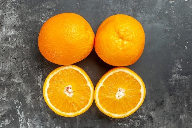Powyżej widok całych i pokrojonych naturalnych organicznych świeżych pomarańczy ułożonych w dwóch rzędach na ciemnym tle