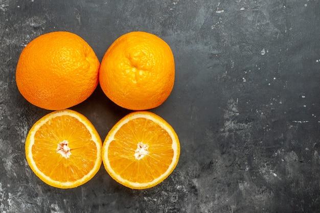 Powyżej widok całych i pokrojonych naturalnych organicznych świeżych pomarańczy ułożonych w dwóch rzędach po prawej stronie na ciemnym tle