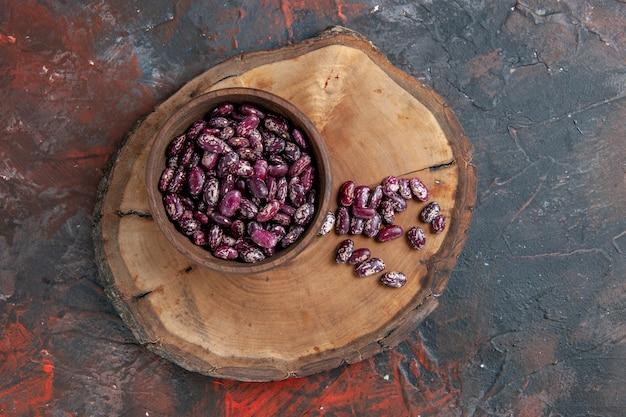 Powyżej widok czarnej fasoli instant w doniczce w brązowej misce na drewnianej tacy na stole mieszanym