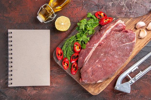 Powyżej widok czerwonego mięsa na drewnianej desce do krojenia czosnek zielony posiekany pieprz opadła butelka oleju i notatnik na ciemnym tle