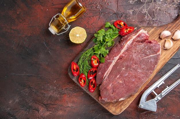 Powyżej widok czerwonego mięsa na drewnianej desce do krojenia i czosnku posiekanego zielonego pieprzu opadłej butelki oleju z cytryną na ciemnym tle