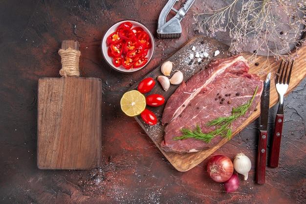 Powyżej widok czerwonego mięsa na drewnianej desce do krojenia i czosnku, zielonej cytryny, cebuli, widelca i noża na ciemnym tle