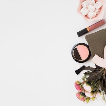 Powyżej widok dekoracji z produktów do makijażu na białym tle
