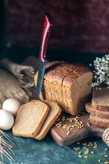 Powyżej widok dietetycznego czarnego chleba pszenicy na drewnianej desce do krojenia nóż kwiat jajka mąka w misce brązowy ręcznik na tle mieszanych kolorów