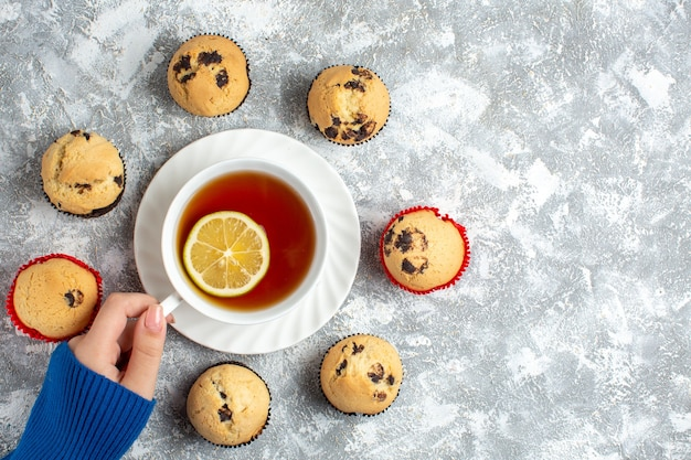 Powyżej widok dłoni trzymającej filiżankę herbaty i pyszne małe babeczki z czekoladą na powierzchni lodu