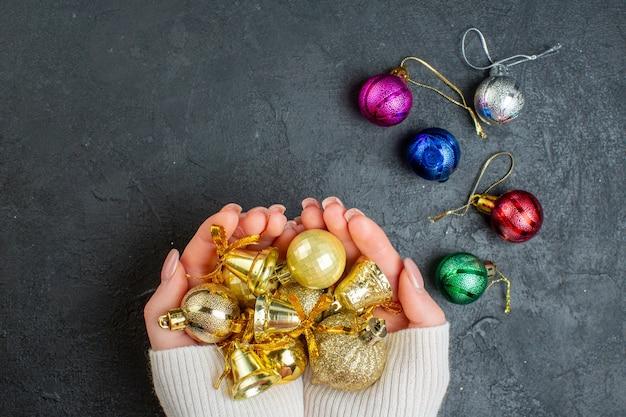 Powyżej widok dłoni trzymającej kolorowe dodatki do dekoracji na ciemnym tle