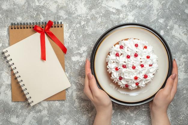 Powyżej widok dłoni trzymającej talerz z pysznym kremowym ciastem ozdobionym owocami obok zeszytów na lodowym tle