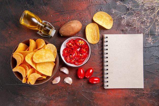 Powyżej widok domowych pysznych chrupiących chipsów ziemniaczanych w brązowym garnku opadła butelka oleju ketchup pomidory ziemniak czosnek i notatnik na ciemnym tle