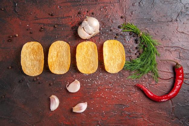 Powyżej widok domowych pysznych czterech chrupiących chipsów czerwona papryka czosnek zielony na ciemnym tle