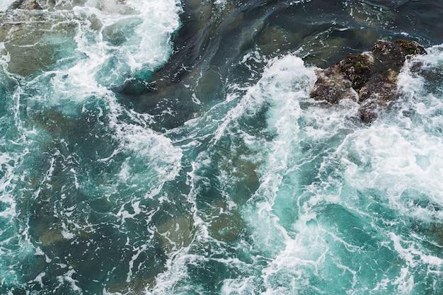 Powyżej widok falistej wody na skalistym brzegu