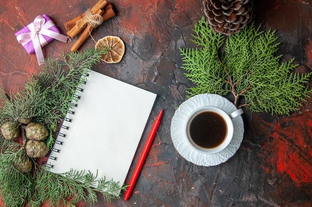 Powyżej widok gałęzi jodłowych fioletowy kolor prezent i zamknięty spiralny notatnik cynamonowe limonki i filiżanka czarnej herbaty na czerwonym tle