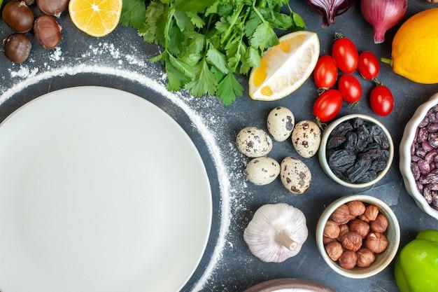 Powyżej widok gotowania obiadu z jajkami, świeże warzywa, zielone wiązki na ciemnoniebieskim