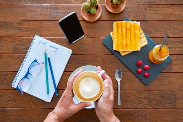 Powyżej widok kącika śniadaniowego z dwiema ludzkimi rękami trzymającymi filiżankę cappuccino z mleczną pianką i kromkami chleba z dżemem na drewnianym stole - notatnik i szklanki