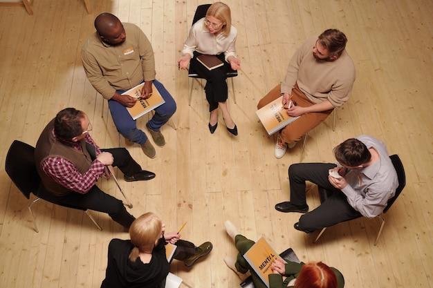 Powyżej widok kilku pacjentów rozmawiających z psychologiem siedzących na krzesłach w kręgu