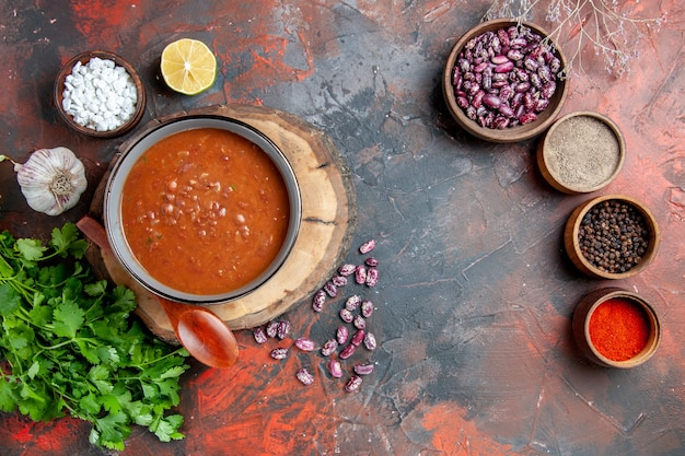 Powyżej widok klasycznej zupy pomidorowej w niebieskiej misce łyżka na drewnianej tacy sól czosnkowa i cytryna pęczek zieleni na stole mieszanym