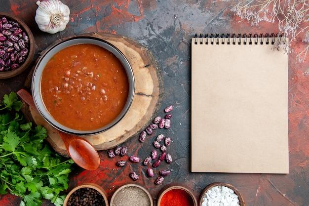 Powyżej widok klasycznej zupy pomidorowej w niebieskiej misce łyżka na drewnianej tacy sól czosnkowa pęczek zieleni i notes na stole mieszanym