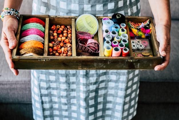 Powyżej widok kobiety biorącej i pokazującej guziki z tkaniny i akcesoria, aby zrobić sukienkę lub biżuterię z dużą ilością kolorów i materiałów - koncepcja biznesowa pracy rzemieślniczej i ręcznej