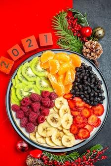 Powyżej widok kolekcji świeżych owoców na talerzu obiadowym akcesoria do dekoracji gałązki jodły i numery świąteczne skarpety na czerwonej serwetce na czarnym tle
