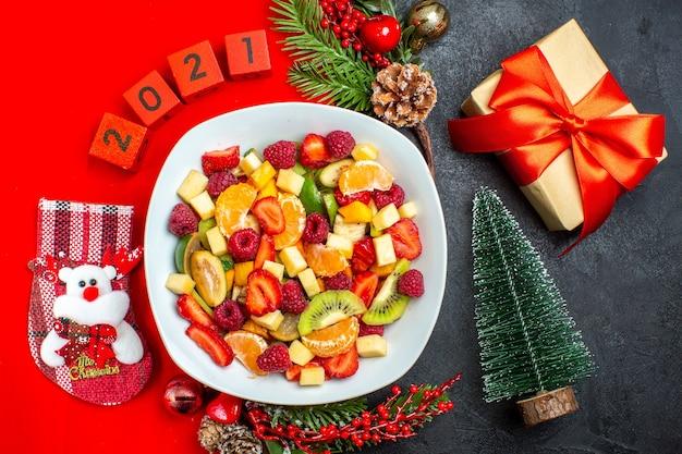 Powyżej widok kolekcji świeżych owoców na talerzu obiadowym akcesoria do dekoracji gałązki jodły numery skarpet świątecznych na czerwonej serwetce i prezentowa choinka na ciemnym tle