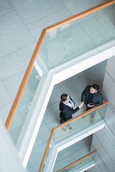 Powyżej widok ludzi biznesu stojących na balkonie i uzgadniających po negocjacjach