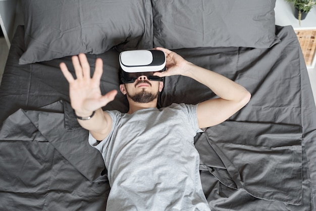 Powyżej widok młodego brodatego mężczyzny zanurzonego w wirtualnej rzeczywistości leżącego na łóżku i oglądającego wideo w goglach vr