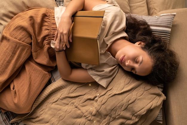Powyżej widok młodej kobiety rasy mieszanej obejmującej pamiętnik podczas snu w łóżku