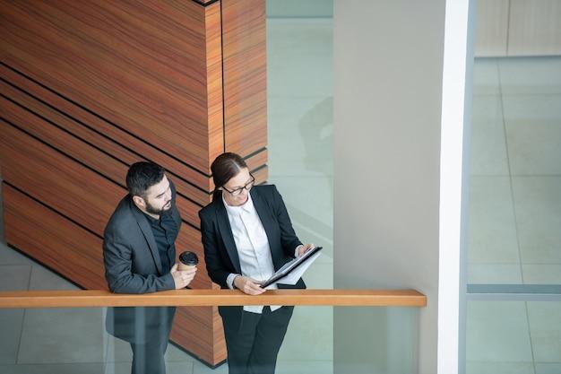 Powyżej widok młodej kobiety w okularach stojącej na balkonie i przedstawiającej kierownikowi dane sprzedażowe w papierach