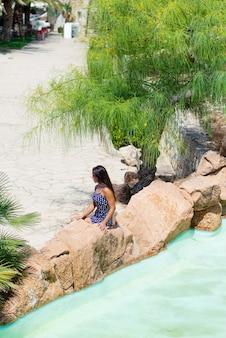 Powyżej widok młodej latynoskiej kobiety siedzącej na skale obok stawu wodnego