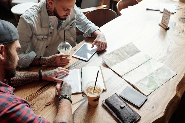 Powyżej widok młodych mężczyzn siedzących przy stoliku w kawiarni i wspólnie planujących trasę przed podróżą