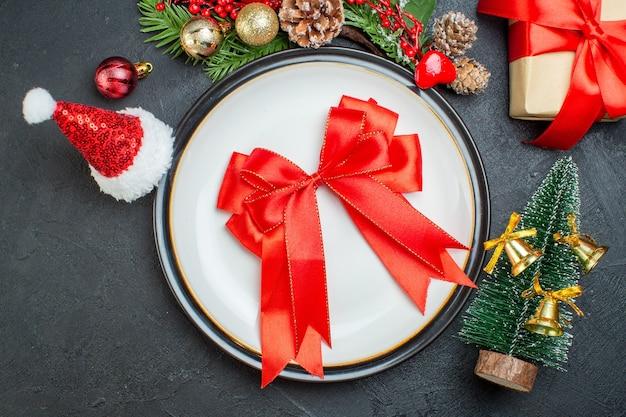 Powyżej widok na czerwoną wstążkę w kształcie łuku na talerzu obiadowym choinka gałęzie jodły szyszka pudełko pudełko czapka świętego mikołaja na czarnym tle