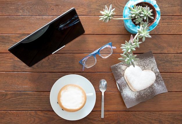 Powyżej widok na drewniany stół przygotowany z gorącym domowym cappuccino i czymś słodkim w kształcie serca. jedno urządzenie technologiczne jako tablet, aby być na bieżąco
