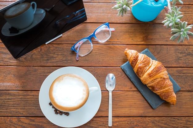 Powyżej widok na drewniany stół z gorącym domowym cappuccino i rogalikiem. jedno urządzenie technologiczne jako tablet, aby być na bieżąco