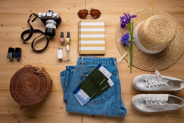 Powyżej widok na dżinsy, kapelusz przeciwsłoneczny, kwiat, aparat fotograficzny, torbę, bilety, lakiery do paznokci i trampki na stole, podróże na knolling