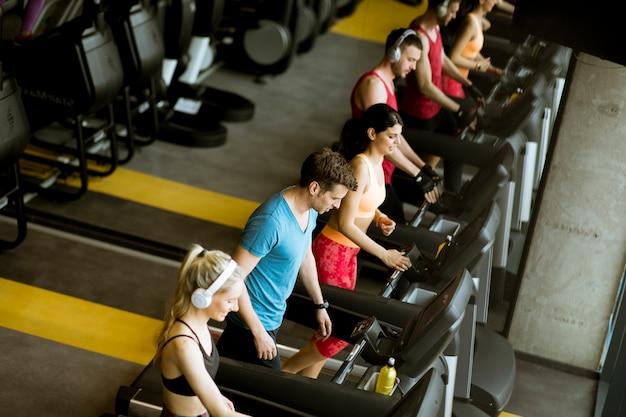 Powyżej widok na grupę młodych ludzi biegających na bieżniach w nowoczesnej siłowni sportowej
