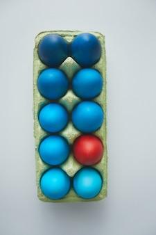 Powyżej widok niebieskich pisanek w skrzynce z czerwonym akcentem ułożonych w minimalnej kompozycji na białym tle, miejsce na kopię