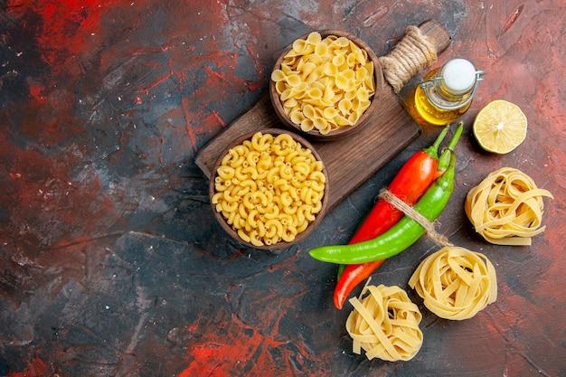 Powyżej widok niegotowanych makaronów papryczki cayenne połączonych ze sobą liną butelka oleju cytrynowy czosnek na stole o różnych kolorach