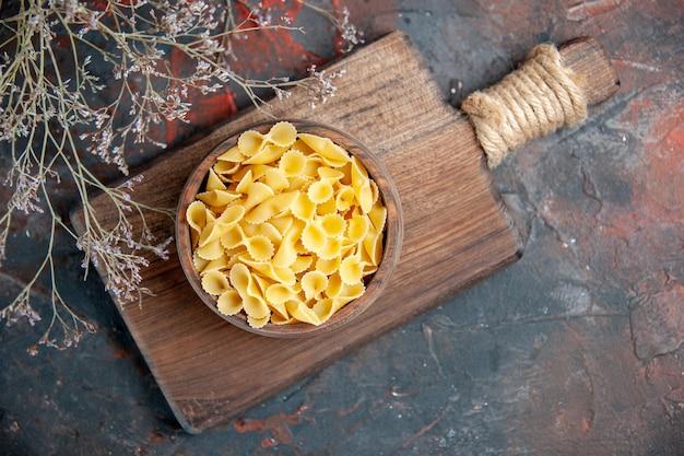 Powyżej widok niegotowanych makaronów w brązowej misce na drewnianej desce do krojenia na stole mieszanym